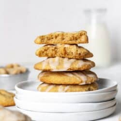 A stack of macadamia nut cookies on a white plate with a glass of milk in the background.